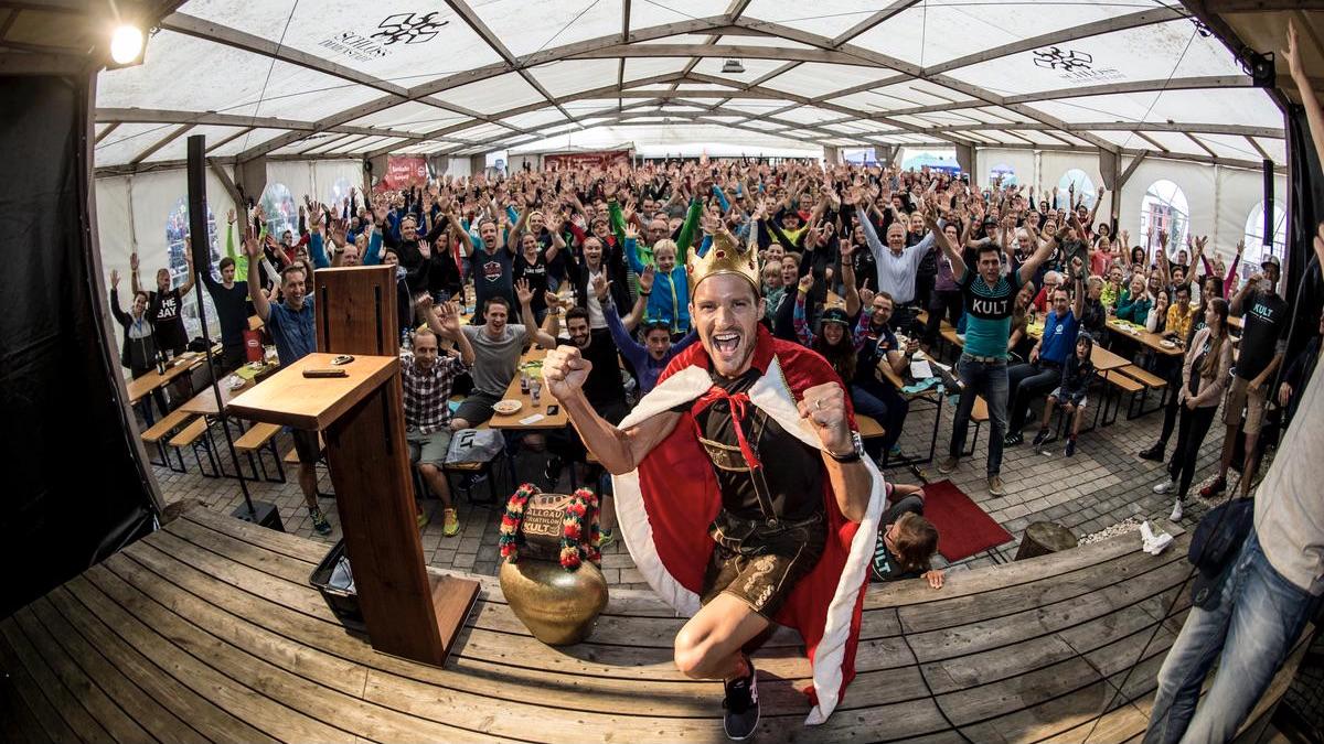 Der Triathlet Jan Frodeno auf der Bühne des Allgäu Triathlons mit einer jubelnden Menschenmasse im Hintergrund