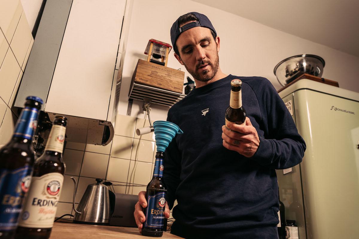 Bocki steht in einer Küche mit einem normalen und einem alkoholfreien Bier in der Hand