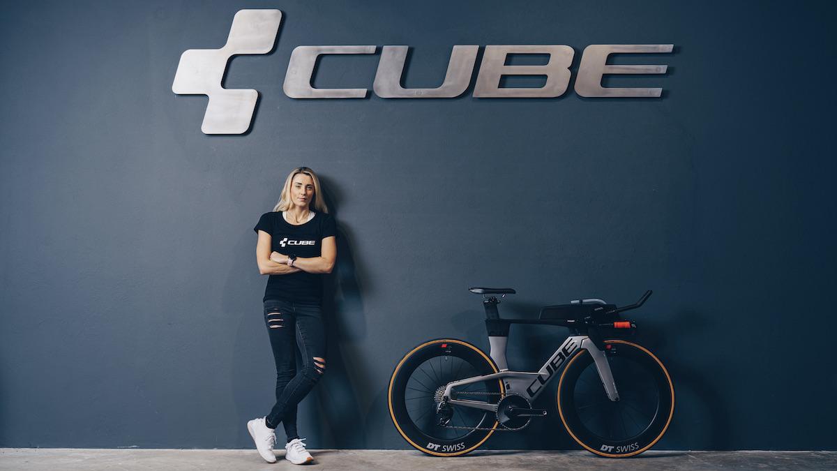Triathletin Lucy Charles-Barclay mit ihrem Rad vor einer Wand mit Cube Logo