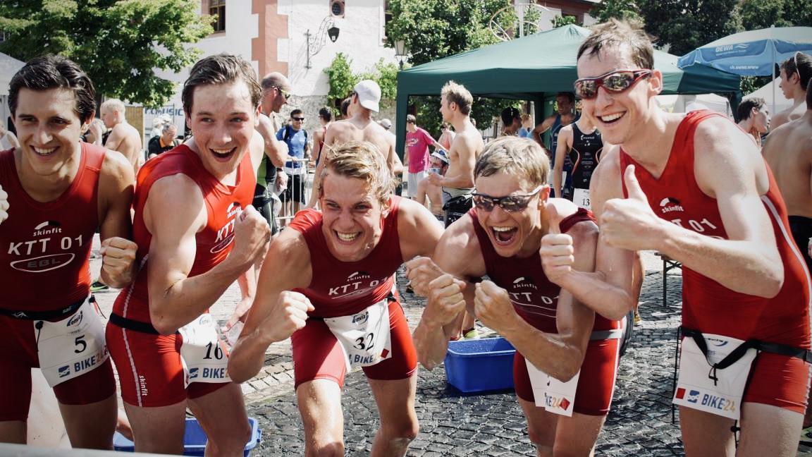 Ein paar Triathleten freuen sich mit Siegerpose im Zielbereich