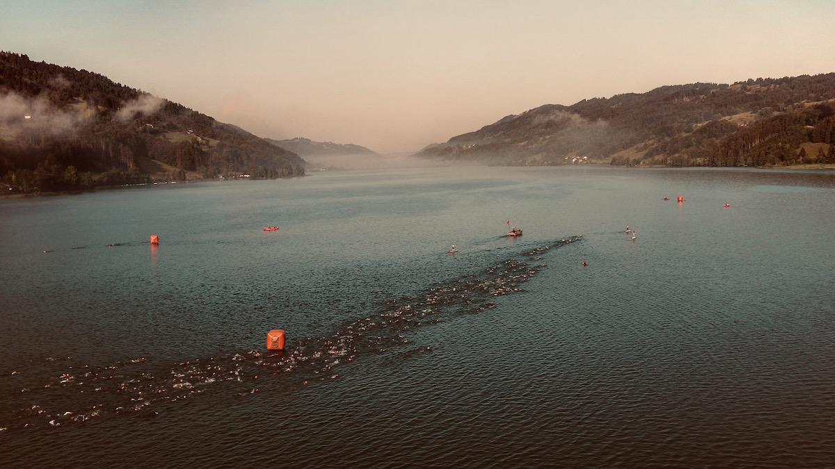 Schwimmer schwimmen bei einem Triathlon in einem von Bergen umgebenen See