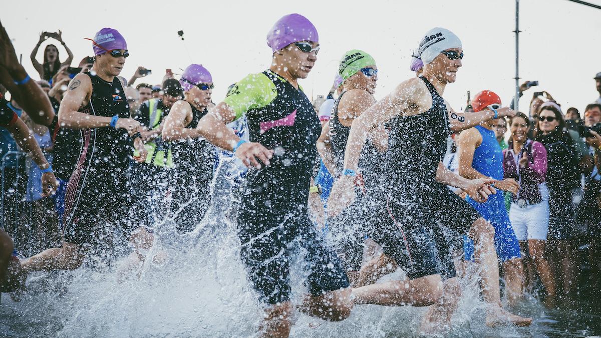Frauen sprinten bei einem Landstart eines Triathlons ins Wasser