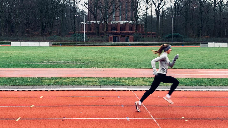 Eine Läuferin läuft im Herbst über eine Tartanbahn