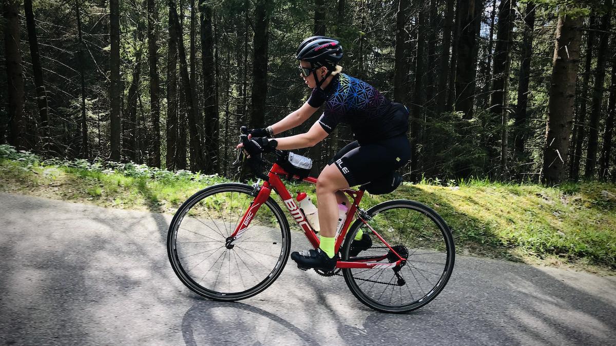 Eine Radfahrerin fährt durch einen Wald eine Straße hinauf
