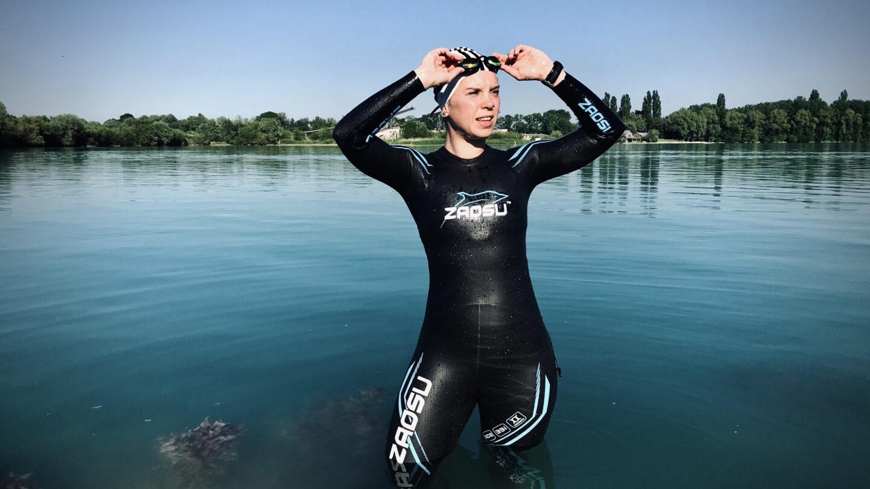 Eine Schwimmerin im Neoprenanzug steht in einem See und setzt sich die Schwimmbrille auf