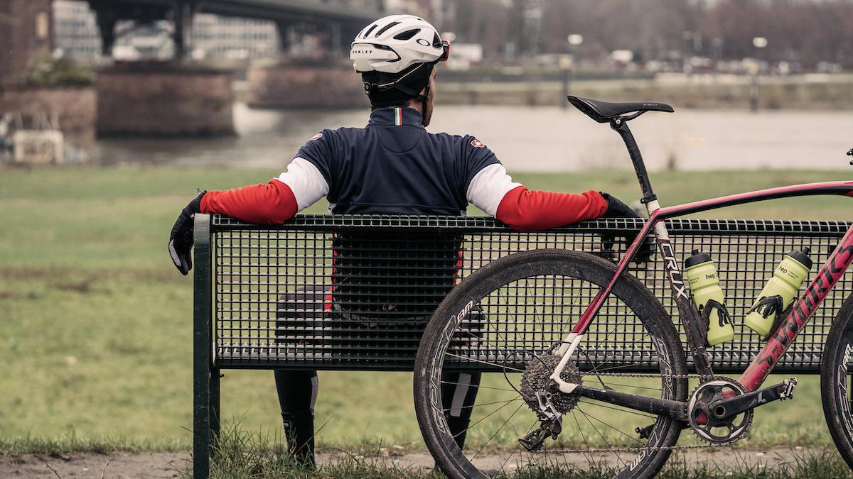 Ein Radfahrer sitzt auf einer Bank an der sein Rad gelehnt ist und schaut auf einen Fluss